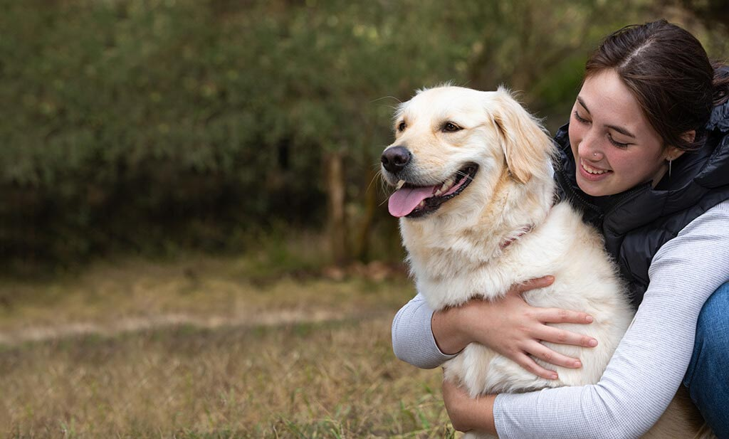 White Labrador cuddling with owner - Pet Insurance by Healthy Paws Pet Insurance